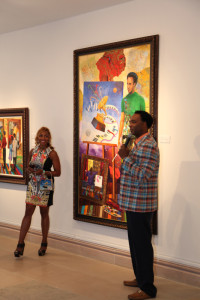 "Yolanda and Marcus Glenn with his new work, ""Accurate Knowledge is Better than Imagination,"" at Park West Gallery."